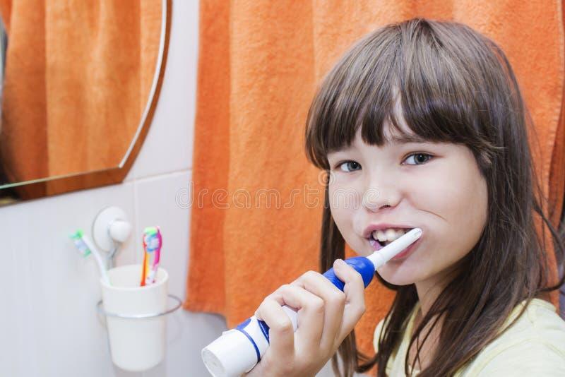 Uma menina da criança que escova seus dentes em uma sala do banho foto de stock royalty free