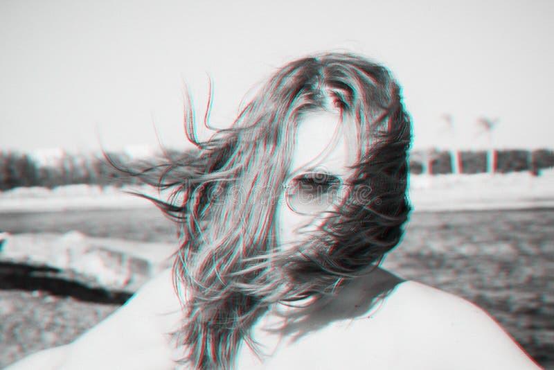 Uma menina de óculos escuros ri, seu cabelo cobre seu rosto, o vento Efekt glitch anaglyph Monocromático preto e branco Retrospec foto de stock
