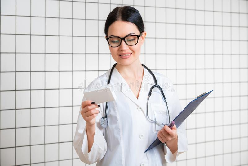 Uma menina de cabelo escuro fina nova com os vidros, vestidos em um macacão médico, lê algo no bloco dos comprimidos ao lado do imagens de stock royalty free