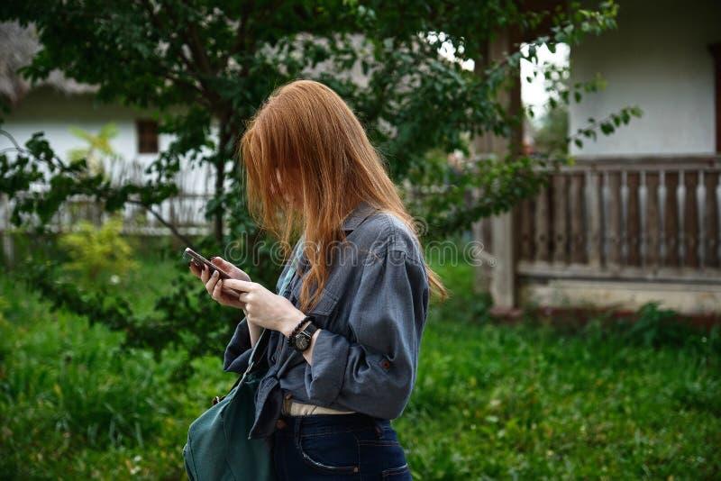 Uma menina de cabelo vermelho em uma camisa de denim fica em perfil com a cabeça curvada e olha para o telefone contra o pano de  fotos de stock royalty free