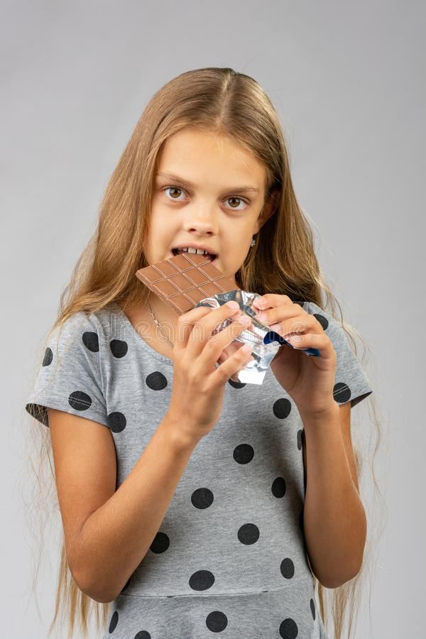 Uma menina de dez anos come uma barra de chocolate fotos de stock
