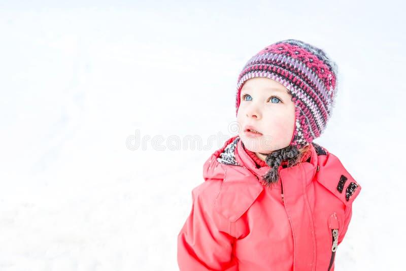 Uma menina de olhos azuis em um chapéu feito malha e em um revestimento cor-de-rosa do inverno olha acima fotografia de stock royalty free