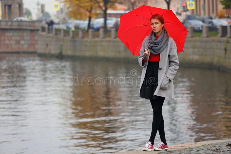 Uma menina de passeio só com guarda-chuva vermelho foto de stock royalty free