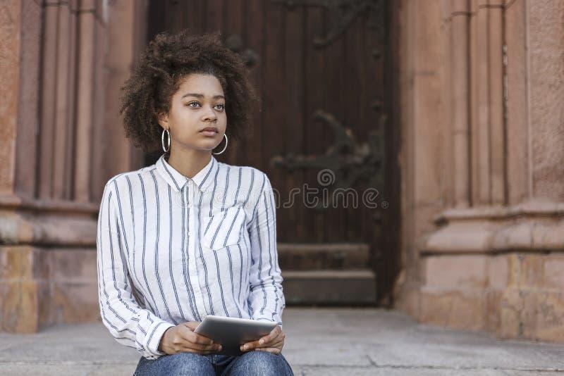 Uma menina de pele escura que senta-se nas etapas perto da construção Olha reta e guarda a tabuleta imagens de stock
