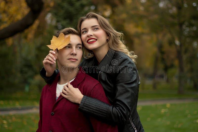 Uma menina de sorriso abraça um indivíduo atrás de seu pescoço, cobrindo uma parte de sua cara com uma cunha, folha amarela de se fotografia de stock