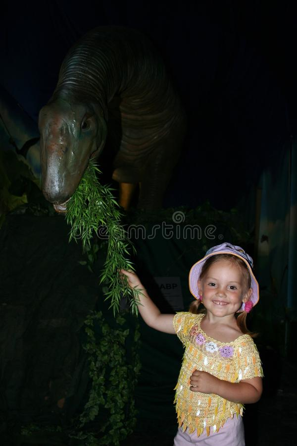 Uma menina de sorriso alimenta o dinossauro pelo ramo verde imagens de stock