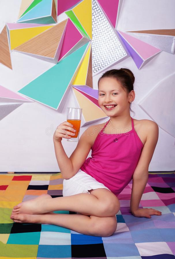 Uma menina de sorriso bonita da criança bebe o suco útil O conceito fotos de stock royalty free