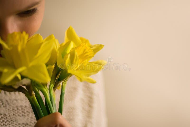 Uma menina de sorriso com um ramalhete da mola amarela floresce, narciso fotos de stock