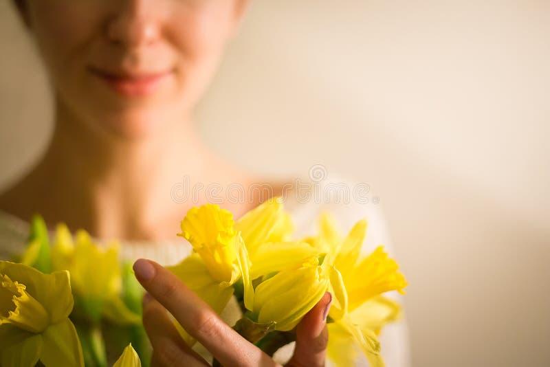 Uma menina de sorriso com um ramalhete da mola amarela floresce, narciso imagens de stock royalty free