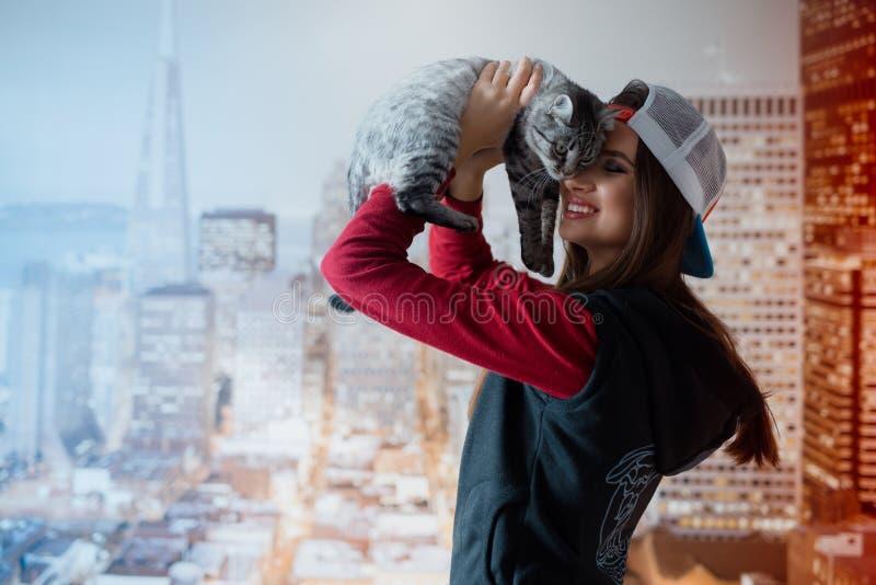 Uma menina de sorriso guarda um gato pela cara imagem de stock royalty free