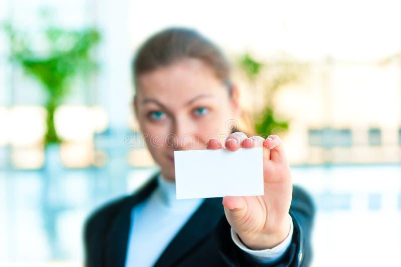 Uma menina de sorriso no traje mostra um cartão vazio fotografia de stock royalty free