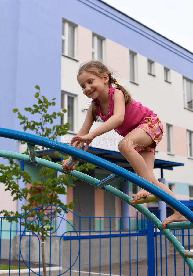 Uma menina de sorriso pequena que usa o material desportivo em um campo de jogos de um house& x27 do apartamento; jarda da corte  foto de stock