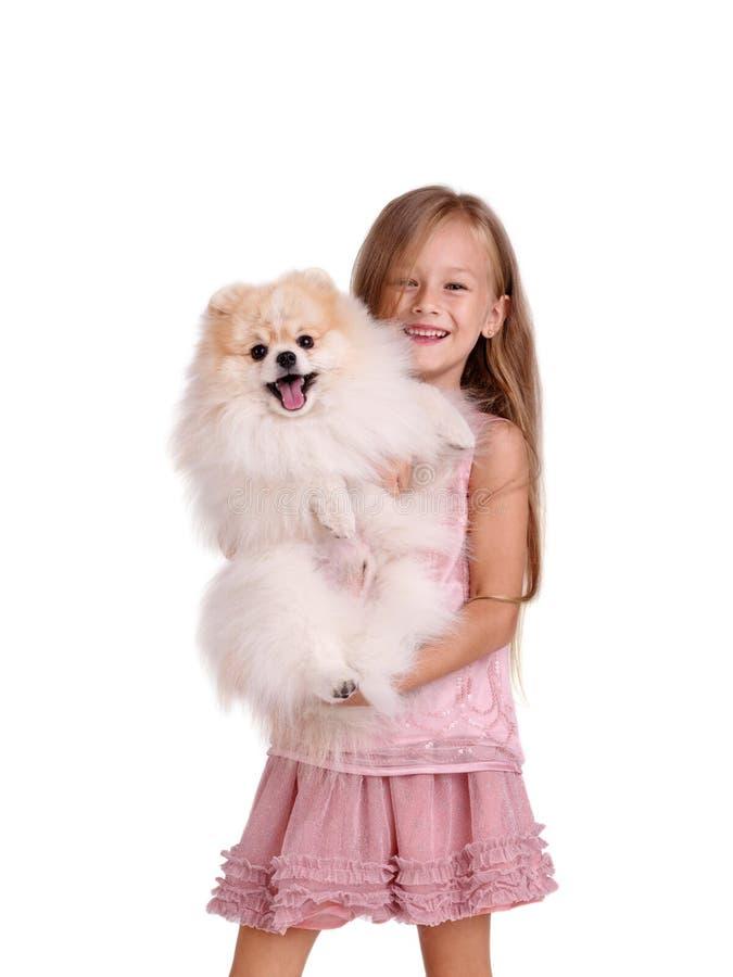 Uma menina de sorriso que guarda um cachorrinho bonito, isolado em um fundo branco Conceito da infância, dos brinquedos e das cri foto de stock royalty free