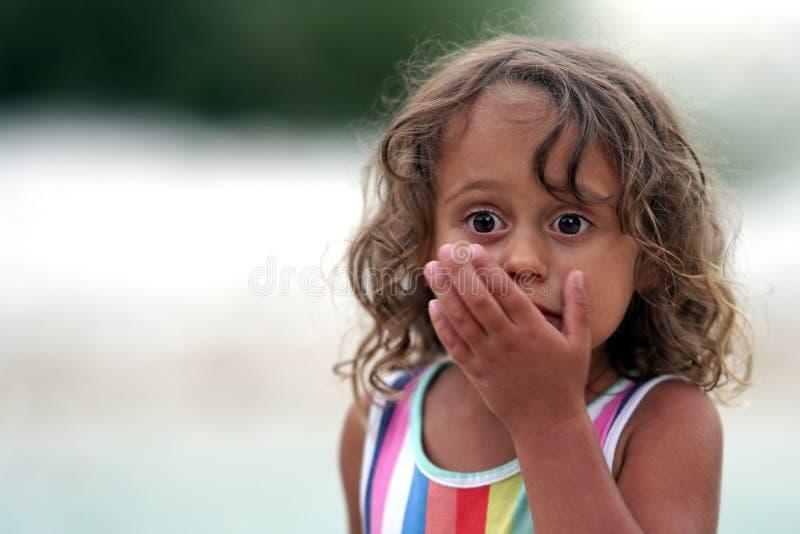 Uma menina de três anos olha preocupada adiante imagens de stock