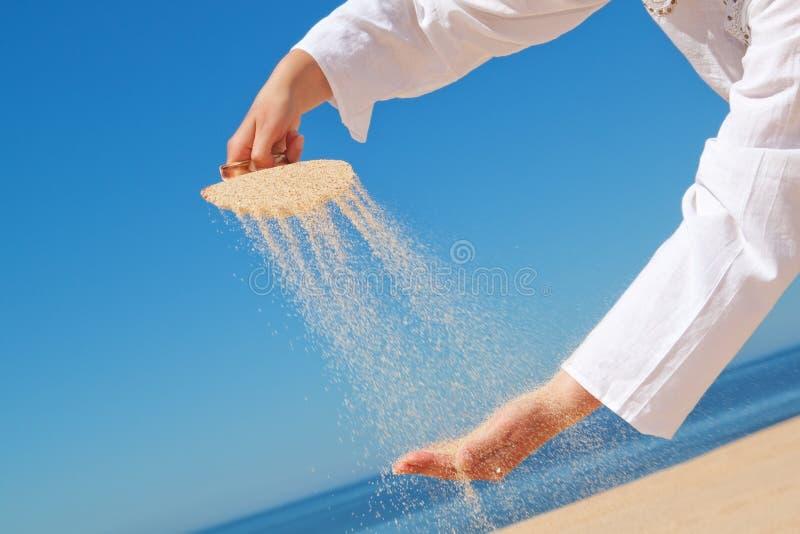 Uma menina derrama a areia fora dos escudos na mão. fotografia de stock royalty free