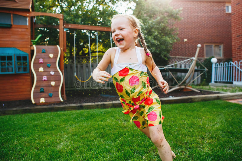 Uma menina desarrumado molhada pequena loura caucasiano adorável bonito que corre no quintal fotografia de stock