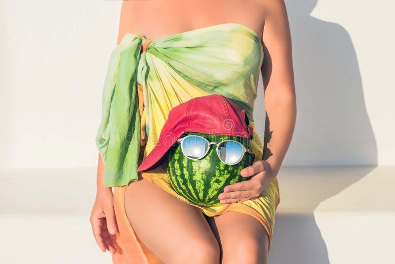Uma menina despida bonita em um pareo que situa em um banco de pedra branco com uma melancia em um tampão e nos óculos de sol em  foto de stock