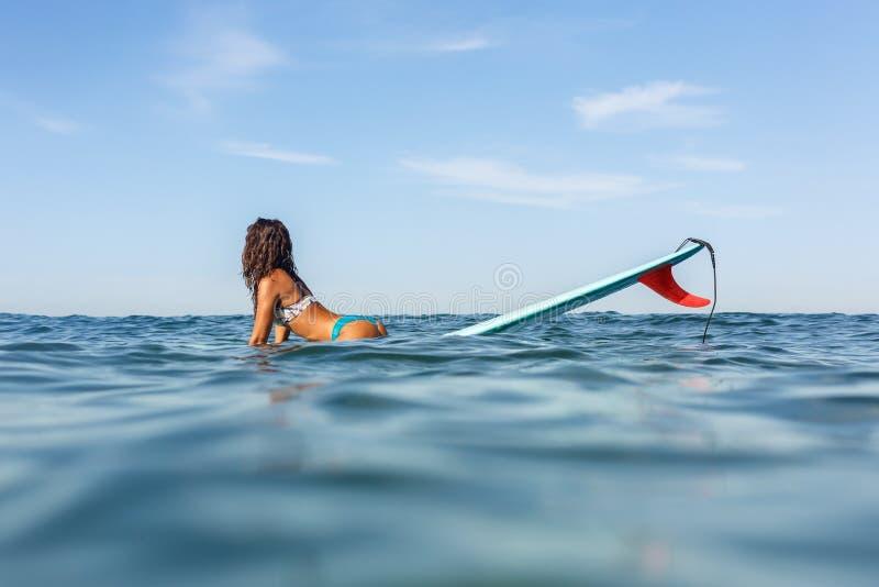 Uma menina desportiva bonita que surfa no oceano imagem de stock royalty free