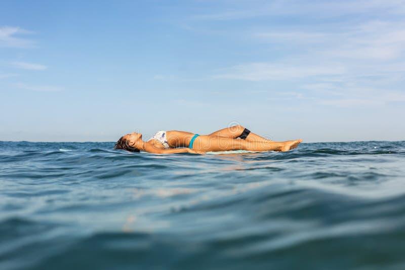 Uma menina desportiva bonita que surfa no oceano imagens de stock royalty free