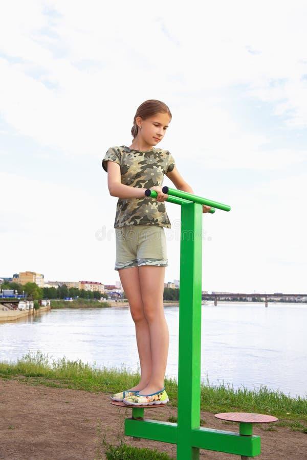 Uma menina do adolescente treina em um simulador do disco em um fundo da cidade imagem de stock royalty free