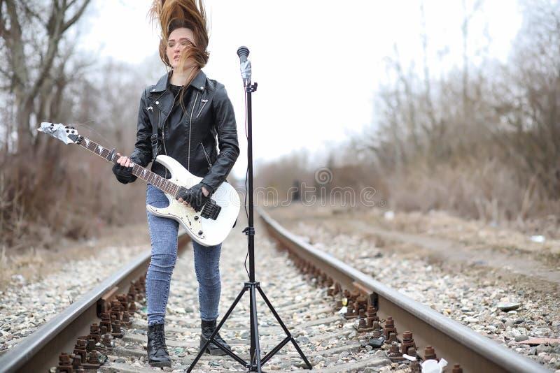 Uma menina do músico da rocha em um casaco de cabedal com uma guitarra imagens de stock royalty free