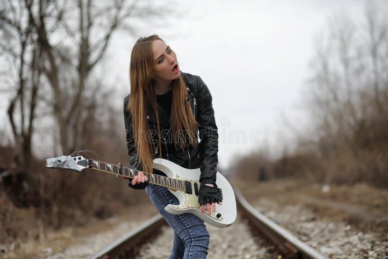 Uma menina do músico da rocha em um casaco de cabedal com uma guitarra fotografia de stock