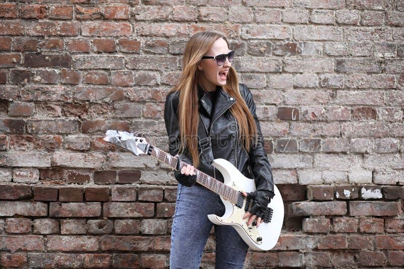 Uma menina do músico da rocha em um casaco de cabedal com uma guitarra fotos de stock