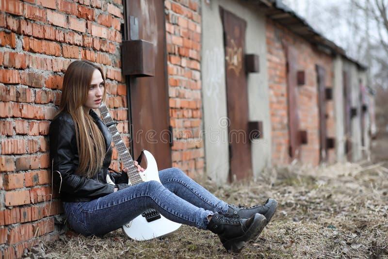 Uma menina do músico da rocha em um casaco de cabedal com uma guitarra imagem de stock royalty free