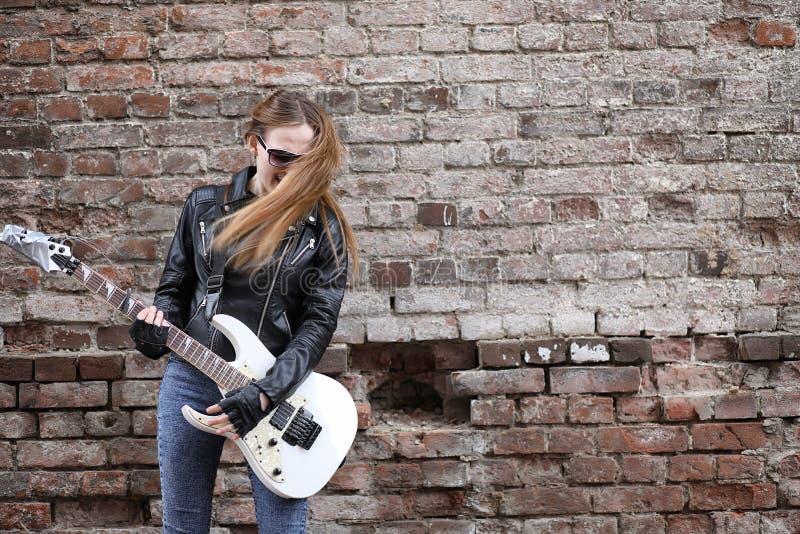 Uma menina do músico da rocha em um casaco de cabedal com uma guitarra imagens de stock