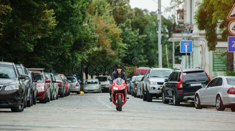 Uma menina do motociclista em um casaco de cabedal em uma motocicleta monta na cidade fotos de stock