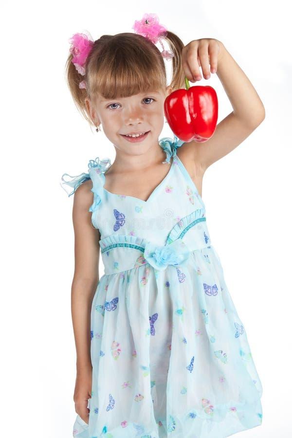 Uma menina doce pequena com uma pimenta vermelha fotografia de stock