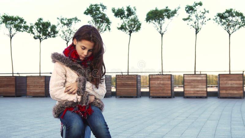 Uma menina doce senta-se no meio da rua e de ser triste fotografia de stock royalty free