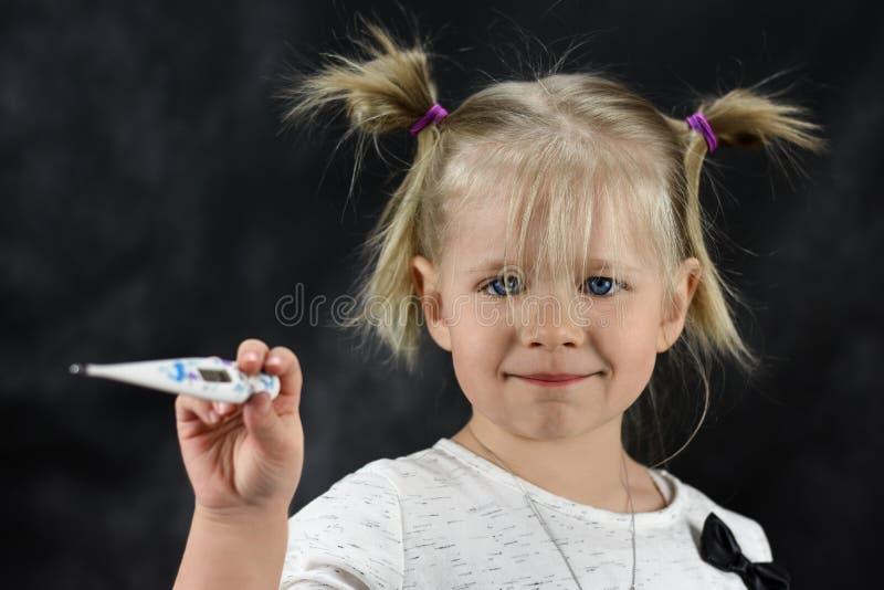 Uma menina doente da criança que guarda um termômetro em sua mão fotografia de stock royalty free