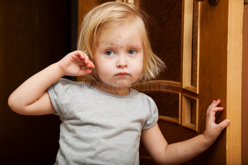 Uma menina doente está perto da porta foto de stock royalty free