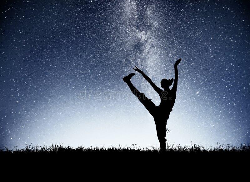 Uma menina dos esportes no alvorecer é contratada na ioga Classes da aptidão no céu estrelado imagem de stock