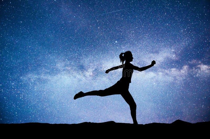 Uma menina dos esportes no alvorecer é contratada na ioga Classes da aptidão no céu estrelado fotos de stock royalty free
