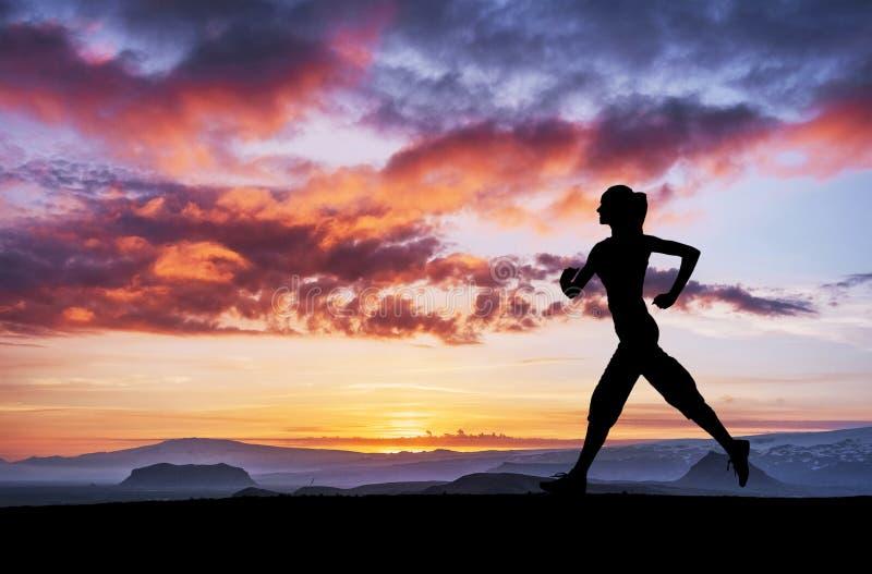 Uma menina dos esportes no alvorecer é contratada na ioga Classes da aptidão no por do sol imagens de stock royalty free