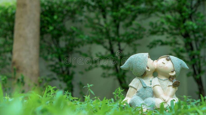 Uma menina e bonecas de um menino, beijando e sentando-se no jardim imagem de stock royalty free