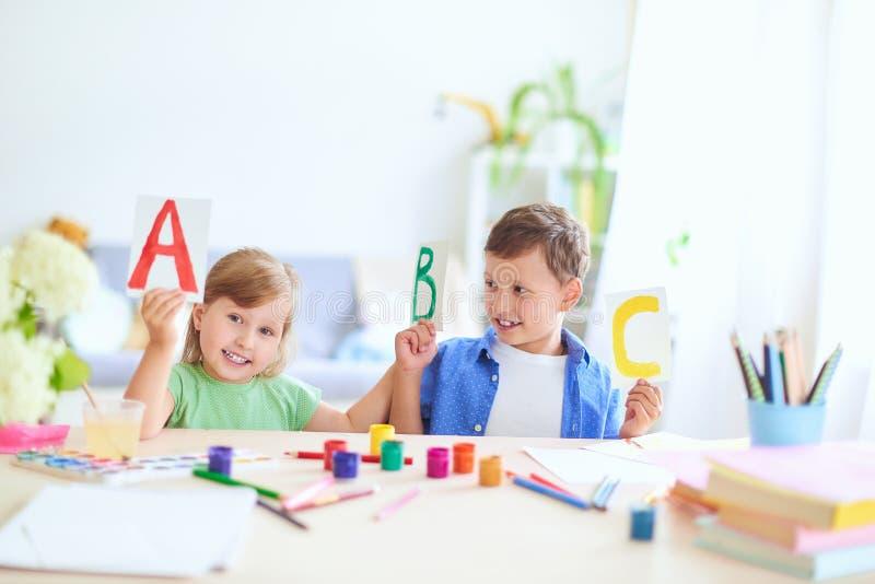 Uma menina e um menino para aprender em casa crianças felizes na tabela com o sorriso das fontes de escola engraçado e a aprendiz imagens de stock royalty free