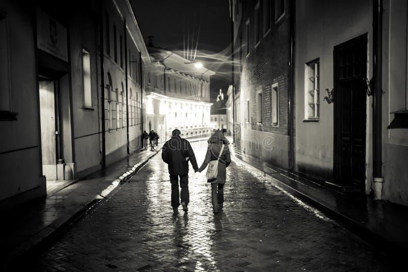 Uma menina e um menino que andam na rua velha da cidade na noite, haldin imagens de stock royalty free