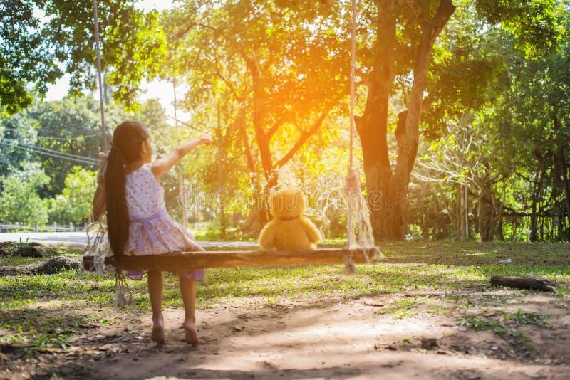 Uma menina e um ursinho sentados em um balanço fotos de stock