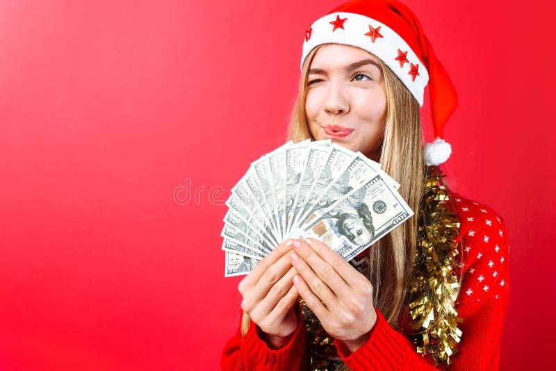 Uma menina em uma camiseta vermelha e em um chapéu de Santa, guarda o dinheiro e os olhares pensando afastado onde gastá-lo em um imagem de stock royalty free