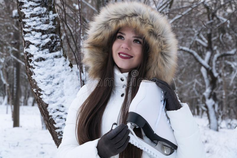 Uma menina em uma capa com patins brancos em um fundo da floresta do inverno imagens de stock