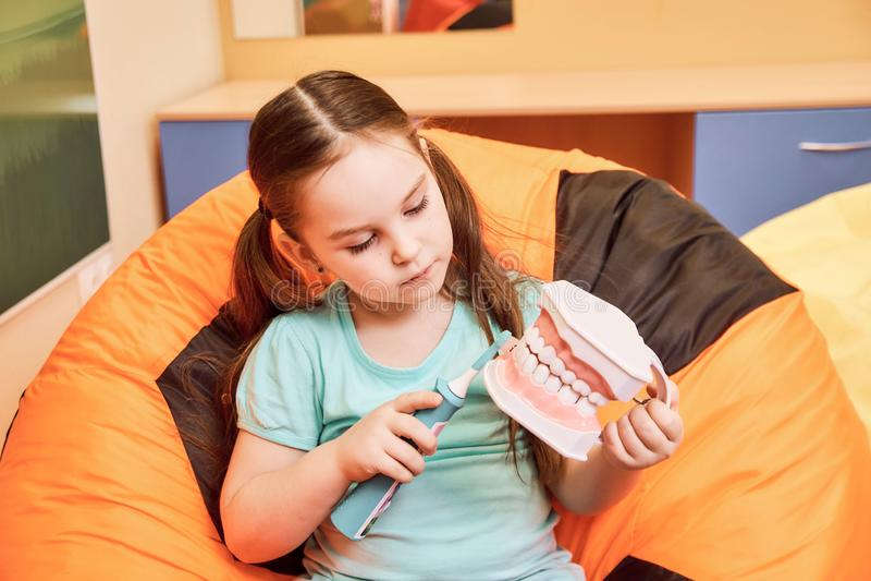 Uma menina em uma clínica dental que guarda um manequim dental fotos de stock royalty free