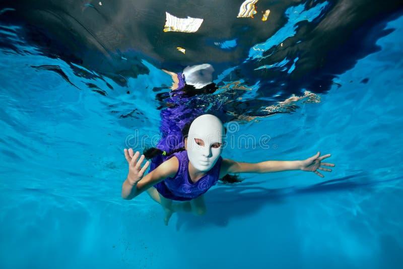 Uma menina em uma máscara branca do disfarce arranja um desempenho teatral, nada debaixo d'água na associação em um fundo azul foto de stock