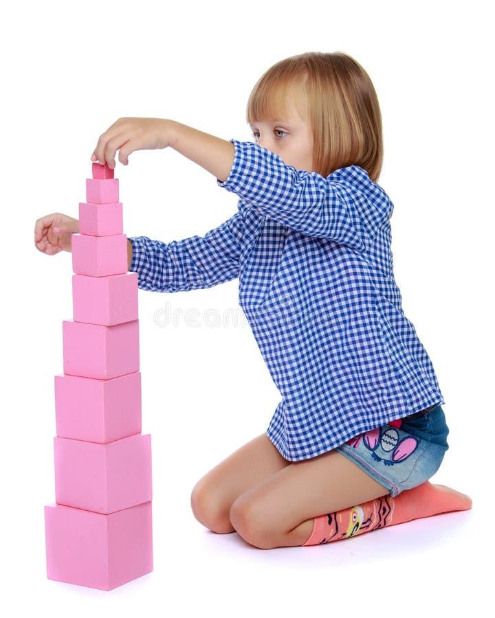 Uma menina em Montessori no jardim de inf?ncia est? jogando com um pi fotografia de stock