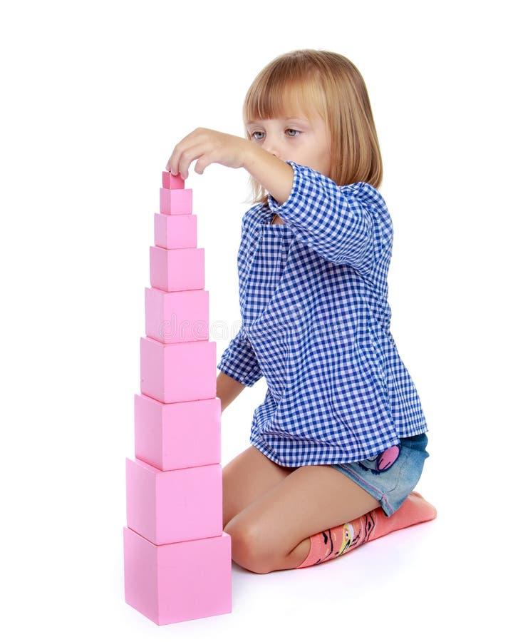 Uma menina em Montessori no jardim de inf?ncia est? jogando com um pi imagem de stock