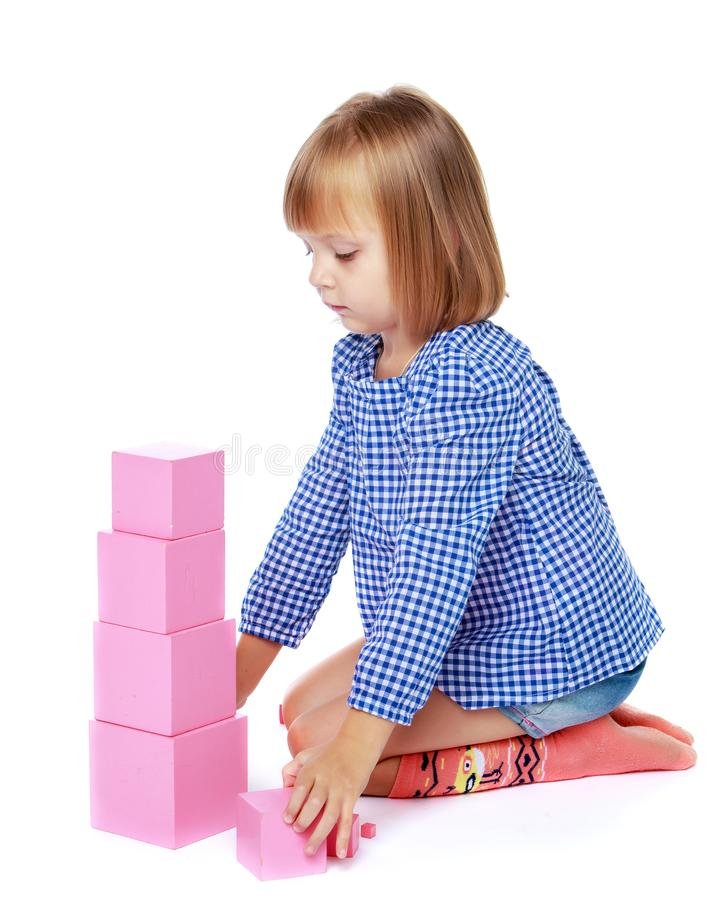 Uma menina em Montessori no jardim de inf?ncia est? jogando com um pi fotos de stock