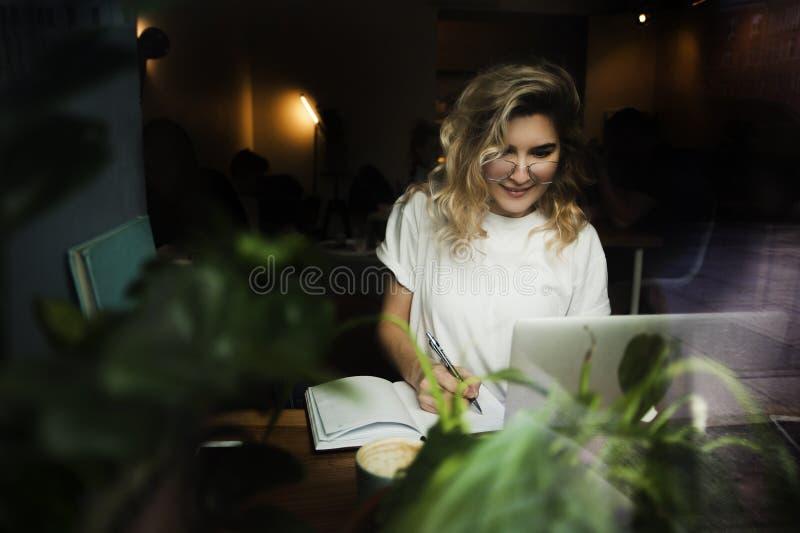 Uma menina em um café com um portátil trabalha em um lugar acolhedor com uma xícara de café, obtém o prazer O conceito de freelan imagem de stock royalty free