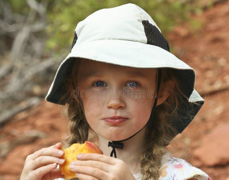 Uma menina em um chapéu branco que come um pêssego fotos de stock